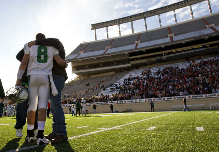 Brenham quarterback  Ty Schlottmann is consoled as he walks off the field after the Cubs' loss to Aledo in the Class 4A Division II state high school football championship game in Austin on Saturday. Photo: Smiley N. Pool, Chronicle
