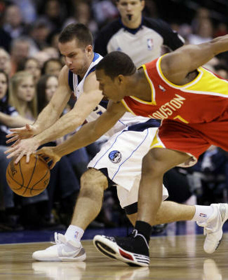Mavericks guard Jose Juan Barea, left, and Rockets guard Kyle Lowry battle for a loose ball in the first half of Friday's game in Dallas. Lowry scored a career-high 26 points to lead the Rockets to a 116-108 victory in overtime. Photo: Tony Gutierrez, AP