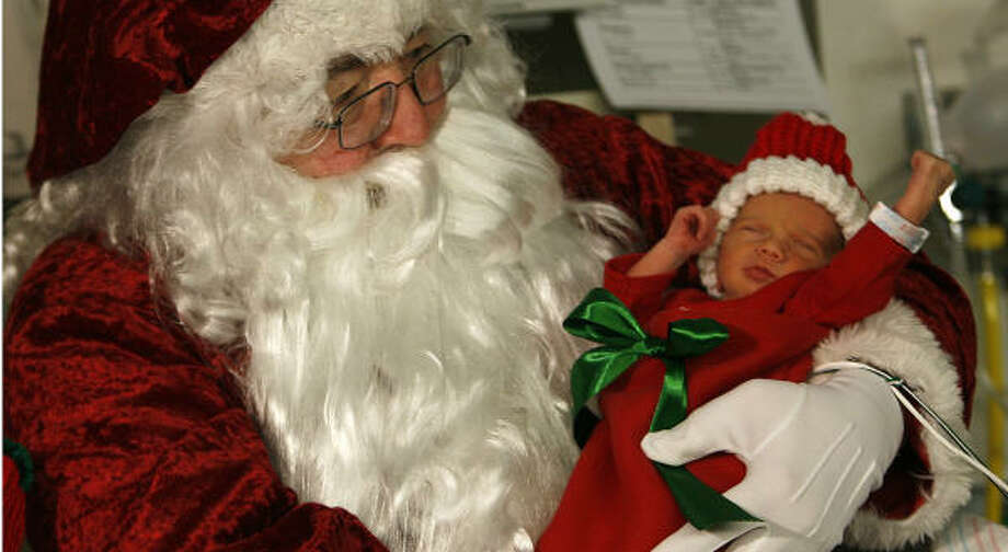 Santa Claus holds four-day-old Peyton Delgado as he and Mrs. Claus visit babies at Memorial Hermann Southwest Hospital Neonatal Intensive Care Unit. Photo: Karen Warren, Chronicle