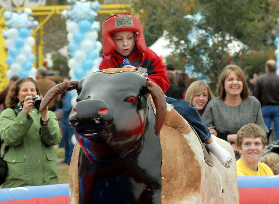 David Lewis,7, rides the mechanical bull at the Lanier Law Firm's Holiday Bash. Photo: Dave Rossman, For The Chronicle
