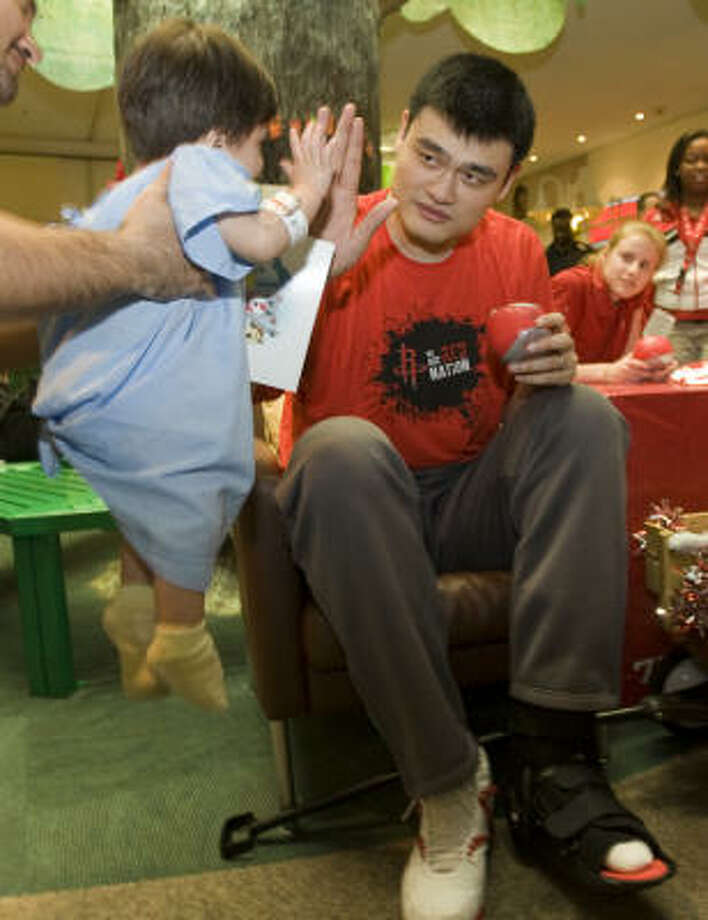 Rockets center Yao Ming, right, high-fives Eric Santos while giving out Christmas gifts to patients at Children's Memorial Hermann Hospital. Rockets players brought gifts and played games with the young patients. Photo: Brett Coomer, Chronicle