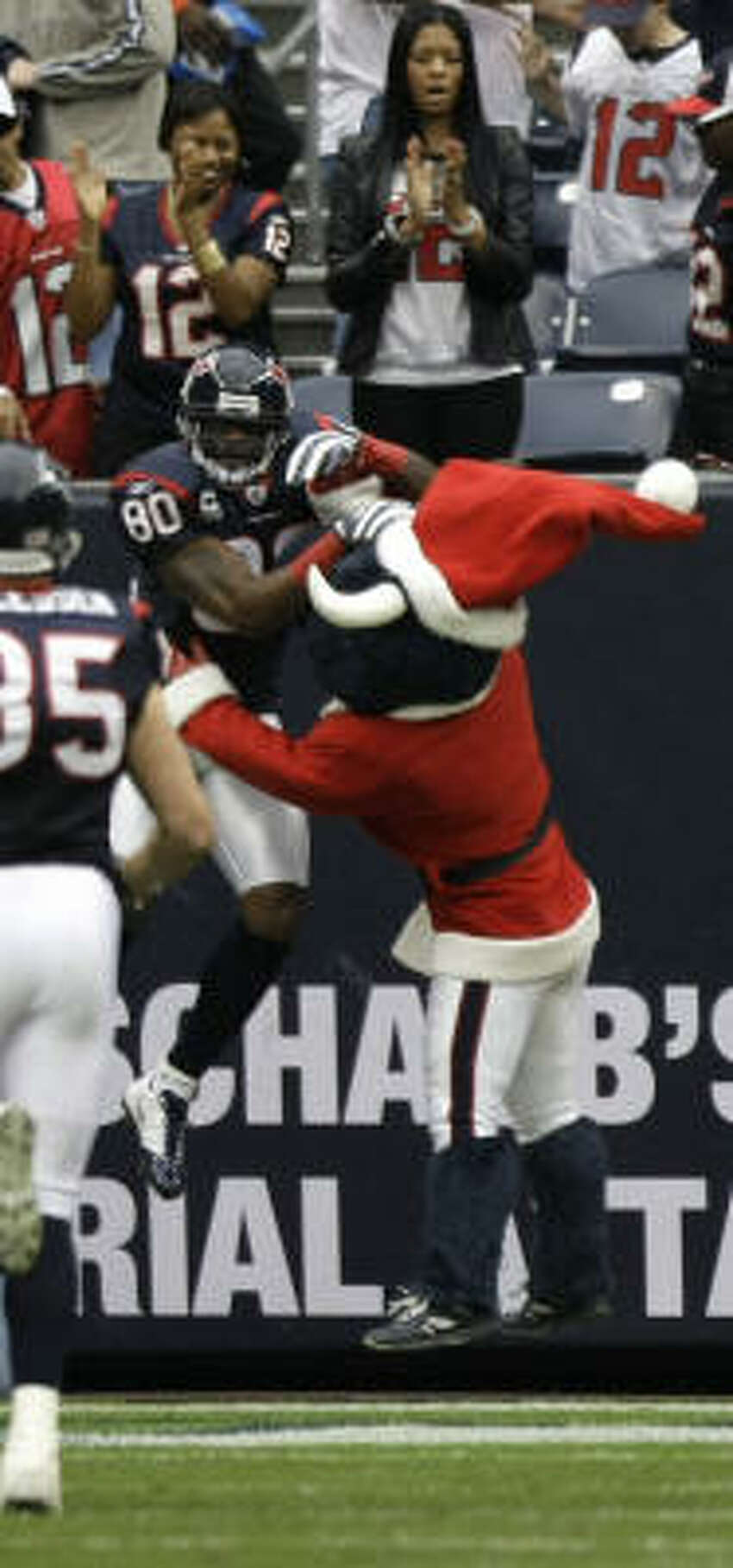 Texans wide receiver Andre Johnson leaps into the arms of Texans mascot Toro after his 64-yard touchdown reception from Matt Schaub on the opening play of the game.