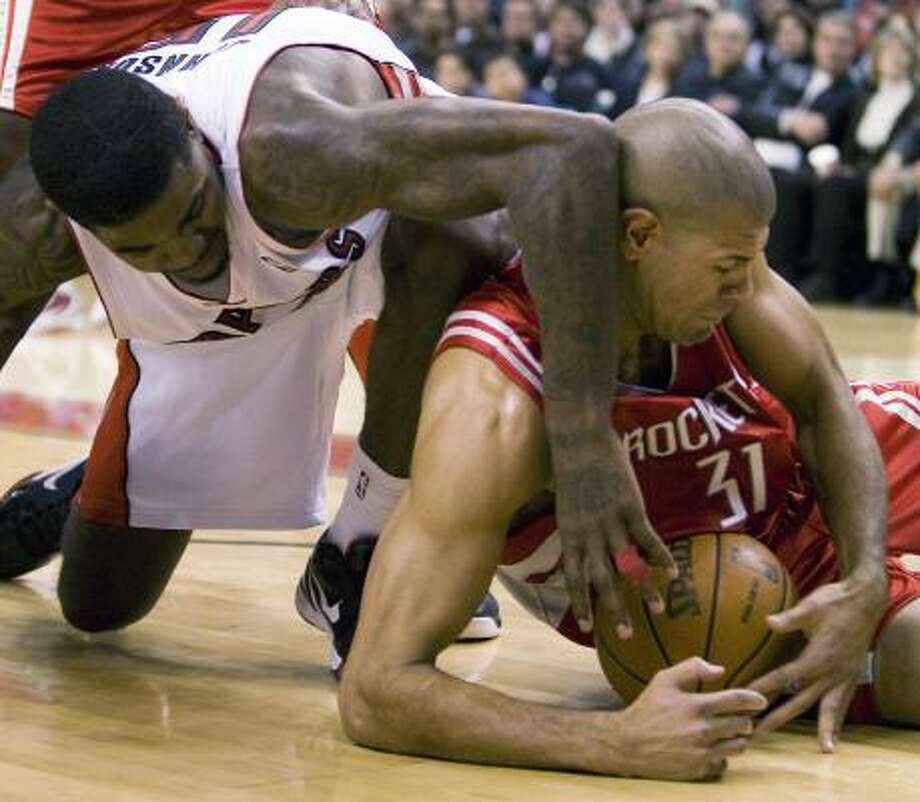 Dec. 13: Raptors 101, Rockets 88 Raptors forward Amir Johnson and Rockets forward Shane Battier battle for a loose ball during the first half. Photo: Frank Gunn, AP