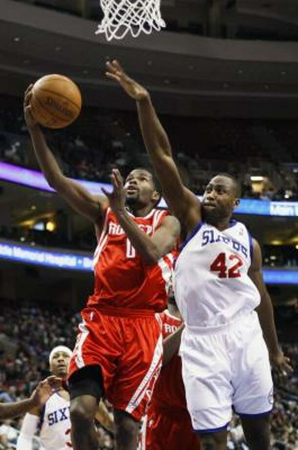 Rockets guard Aaron Brooks, left, goes up for a shot over 76ers forward Elton Brand in the second half of Friday's game. Brooks scored 19 points to lead the Rockets past the 76ers, 96-91. Photo: Matt Slocum, AP