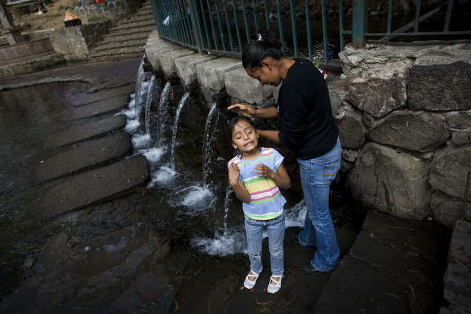 Tania Castro, 24,  washes the hair of Areli Gonzalez Castro, 7, her daughter,  with holy water in Ahuehuete, the first stop in the holy pilgrimage to Chalma.  It is believed that the water, which springs from underneath an enormous tree, is holy and that one should cleanse with it before arriving at the church in Chalma. Photo: David Rochkind, For The Chronicle