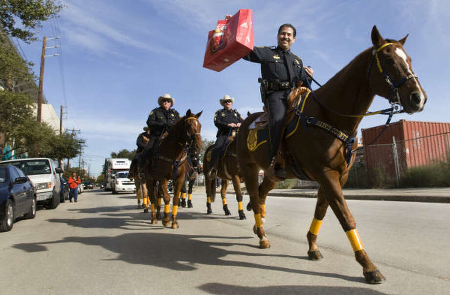 Sheriff Adrian Garcia carries a gift on horseback as he and his deputies deliver toys to the children being served by the Children's Assessment Center. Deputies delivered 2,000 toys donated by the officers of the department. Photo: Brett Coomer, Chronicle