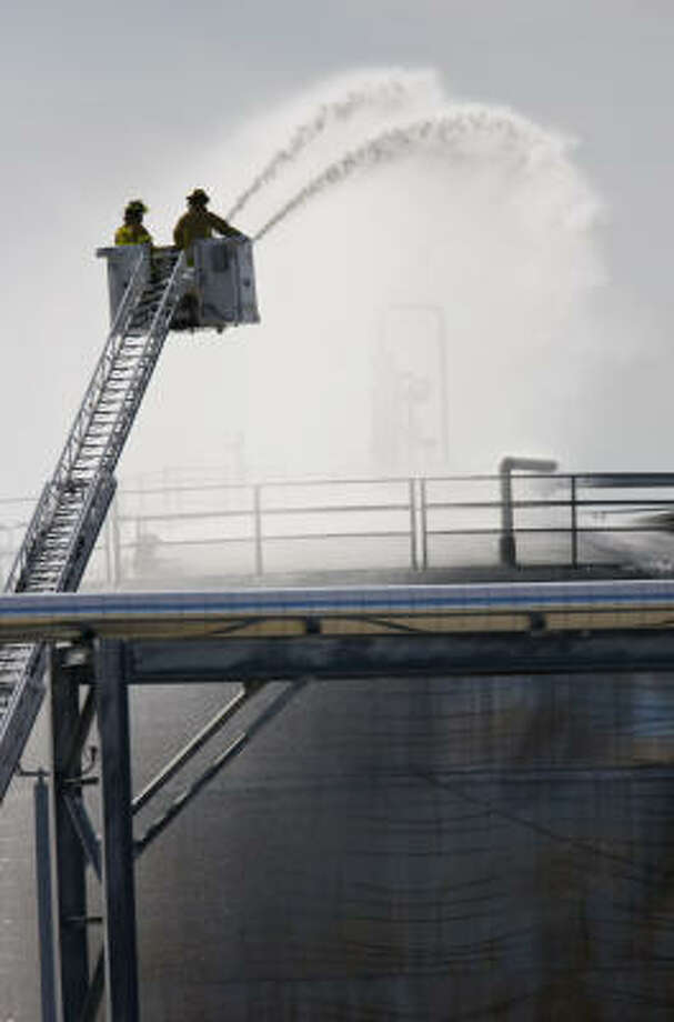 Firefighters pour water on a tank at the American Acryl plant near Pasadena today. Photo: Karen Warren, Chronicle