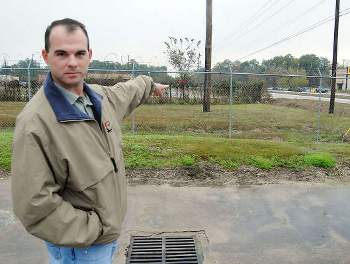 Brian Boyd, an employee at Crane Works on Tidwell, points to a ditch where he spotted fugitive Arcade Joseph Comeaux Jr. as he arrived at work Monday morning.