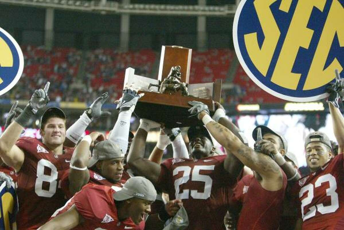 Alabama 32, Florida 13 Alabama players celebrate with the trophy after winning the SEC title game.