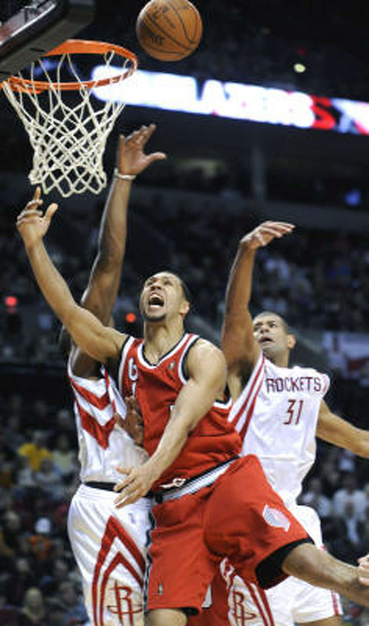 Trail Blazers guard Brandon Roy scores in front of Shane Battier (31) and Carl Landry (14) during the final minutes.