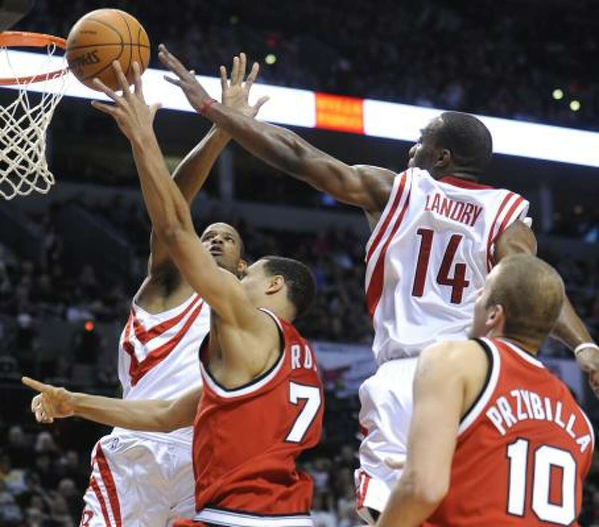 Trevor Ariza, left, and Carl Landry (14) defend a shot by Trail Blazers guard Brandon Roy (7).