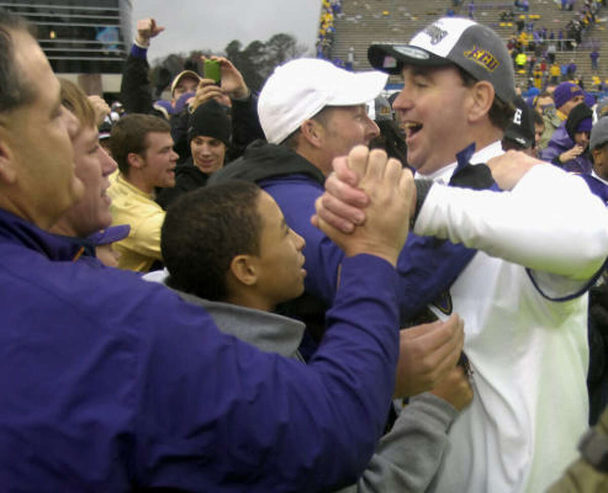 East Carolina coach Skip Holtz, right, is congratulated by fans.