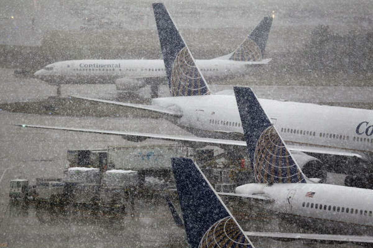 Snow falls at Bush Intercontinental Airport on Friday. Several flights were canceled at both Bush and Hobby Airport.