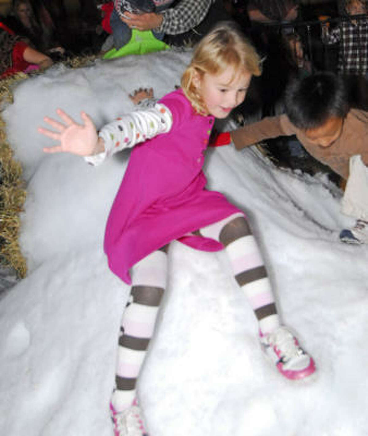 Five-year-old Pia Ekeberl (cq) slides down the snow hill during the 6th Annual Community Christmas Tree Lighting ceremony at The Fellowship at Cinco Ranch Nov. 29.