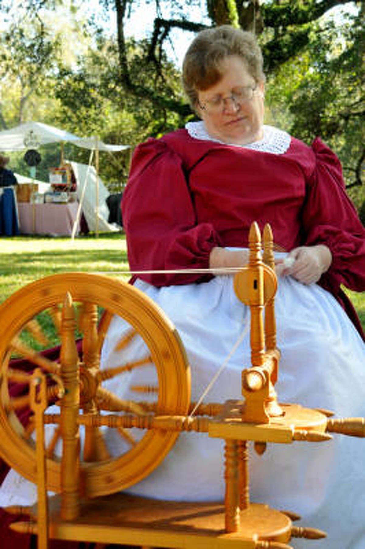 CIVIL WAR WEEKEND: Peggy Barnette uses an old-fashioned spinning wheel during the Civil War Weekend held at Liendo Plantation. Barnette was taught how to spin by her best friend. The fleece has to be washed and carded before spun into thread or yarn. A man made this wheel for his wife in 1970 and when she passed away, he sold to Peggy.