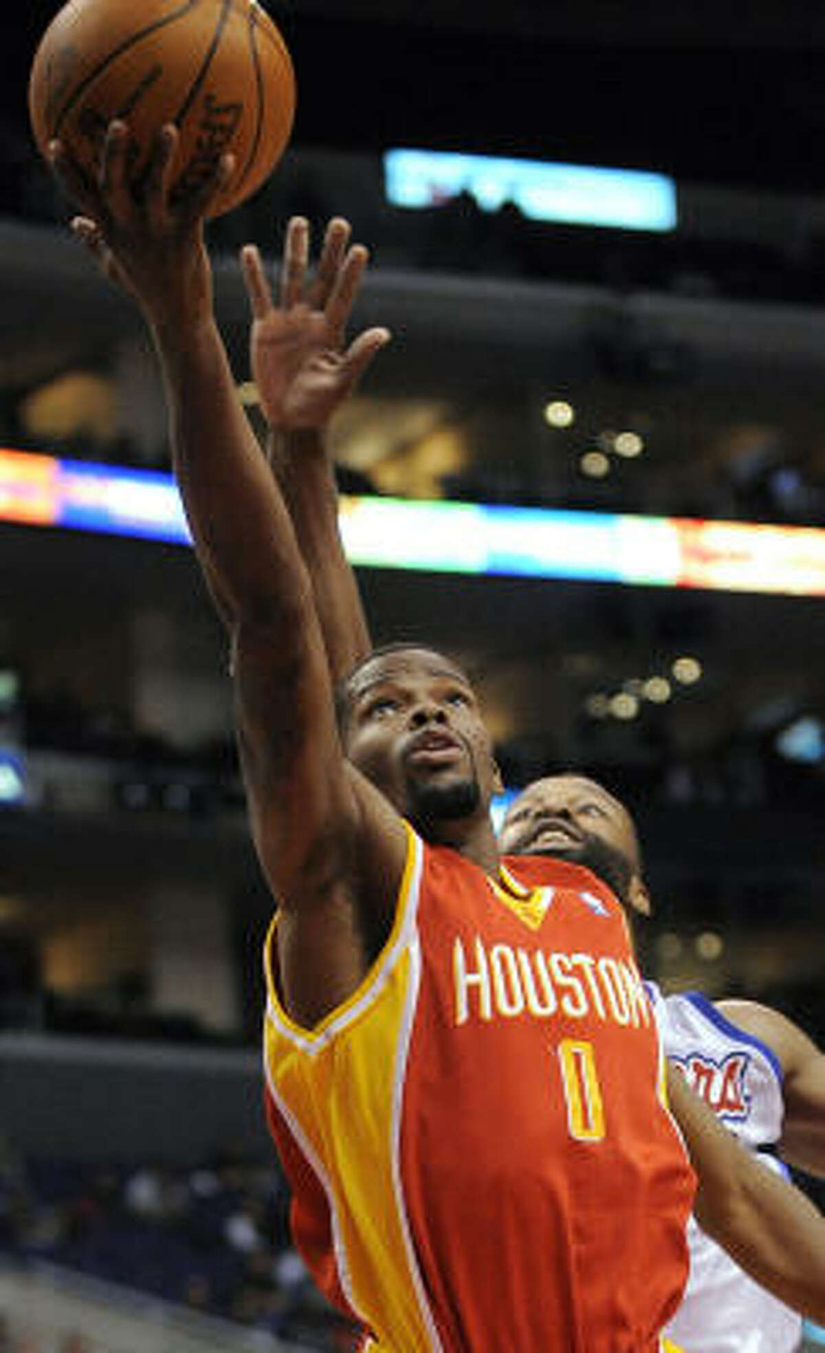 Rockets guard Aaron Brooks goes up for a shot as Clippers guard Baron Davis defends during the first half.