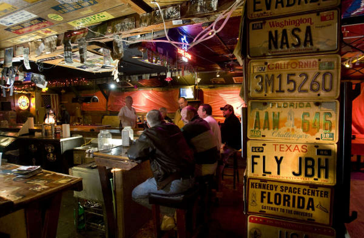 Patrons of the Outpost Tavern gather at the bar Wednesday, Dec. 2, 2009, in Webster. The venerable NASA hangout, known for its bikini-clad swinging doors and priceless space memorabilia, will be closed next month after the property on which the bar stands has been sold. The new owners plan to build something new on the site.