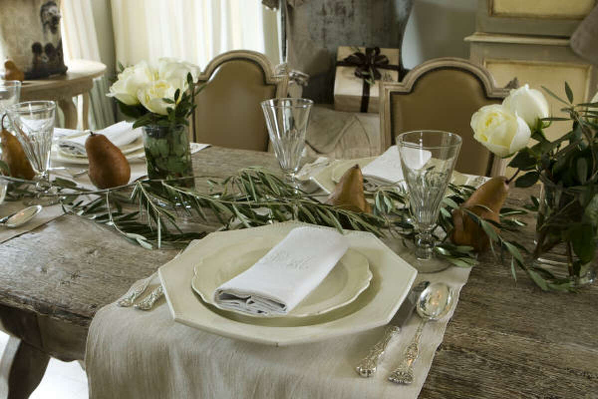 For the Museum District home of Dr. Devinder and Gina Bhatia, she and Megan Talley layered the painted French trestle dining table with olive branches, brown pears and white roses. Vintage linens, glassware and flatware, along with antique French dinnerwa