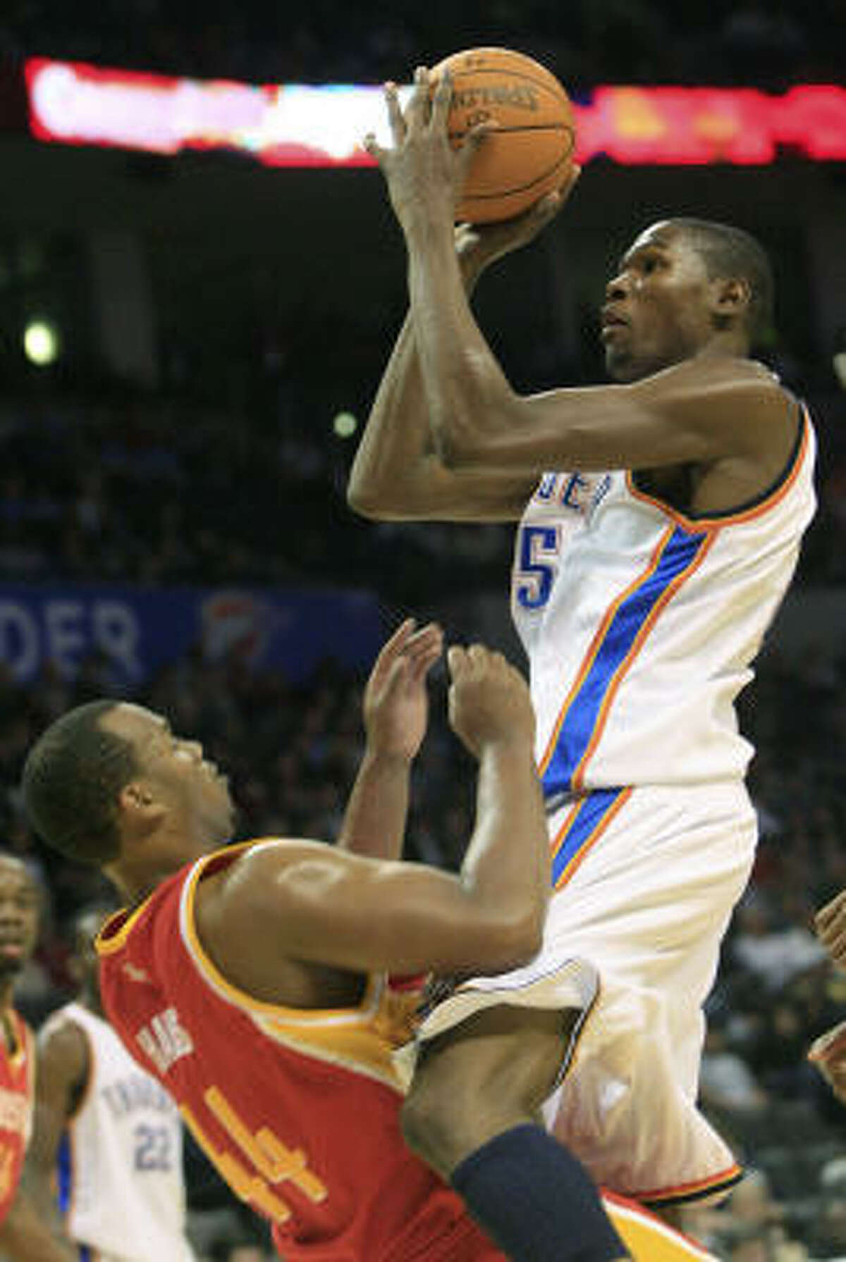 Thunder forward Kevin Durant, right, chargers into Rockets center Chuck Hayes as he goes up for a shot in the third quarter. Durant, who was called for an offensive foul on the play, finished with 25 points.