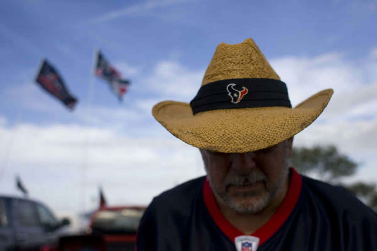 Texans fan David Tiger prepares for the game against the Colts by grilling in the parking lot of Reliant Stadium.