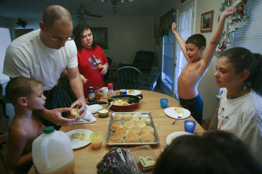 Texas National Guardsman Bernie Hanus, 38, shares breakfast with his family before church in July. From left, son James, 5, wife Brandy, 37, son Michael, 8, and daughter Megan,12.  Bernie will deploy to Iraq at the end of this year with the Houston-based 72nd Infantry Brigade Combat Team. Photo: Mayra Beltran, Chronicle