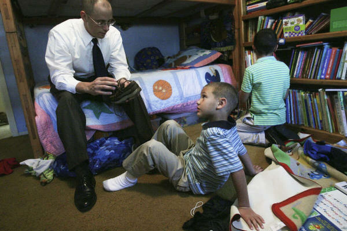 Hanus helps James put on his shoes as Michael finishes getting ready before church in July.