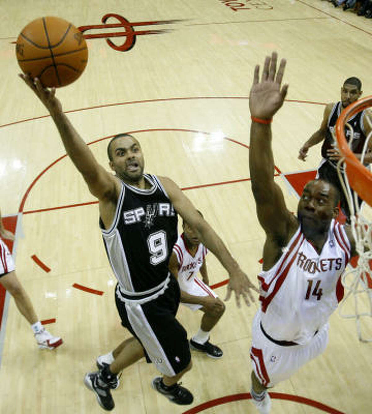 Spurs guard Tony Parker (9) drives to the basket past Rockets forward Carl Landry (14) during the second half. The Spurs beat the Rockets, 92-84.