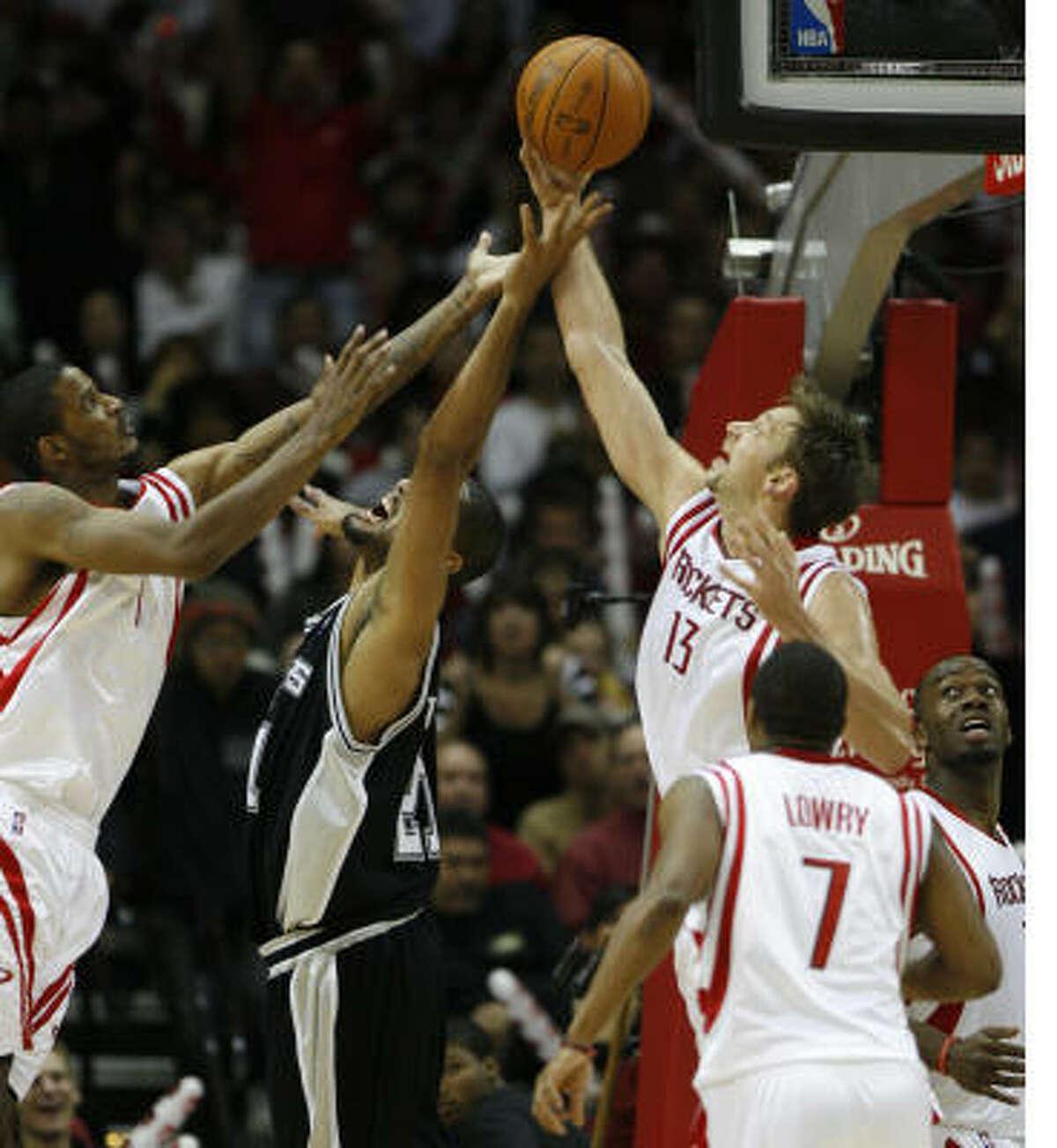 Rockets forward Trevor Ariza, left, and center David Andersen (13) battle for a rebound against Spurs center Tim Duncan during the second half.