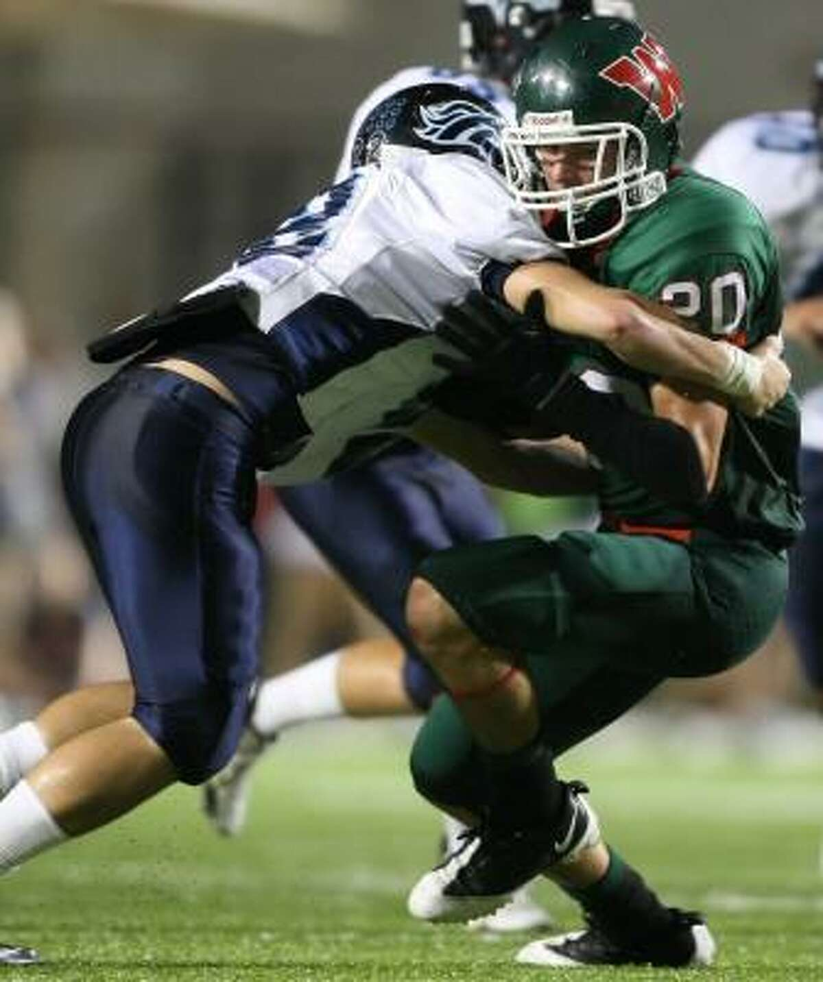 The Woodlands' Jackson LaPlant, right, gets tackled by Kingwood's Brad Tice late in the fourth quarter.