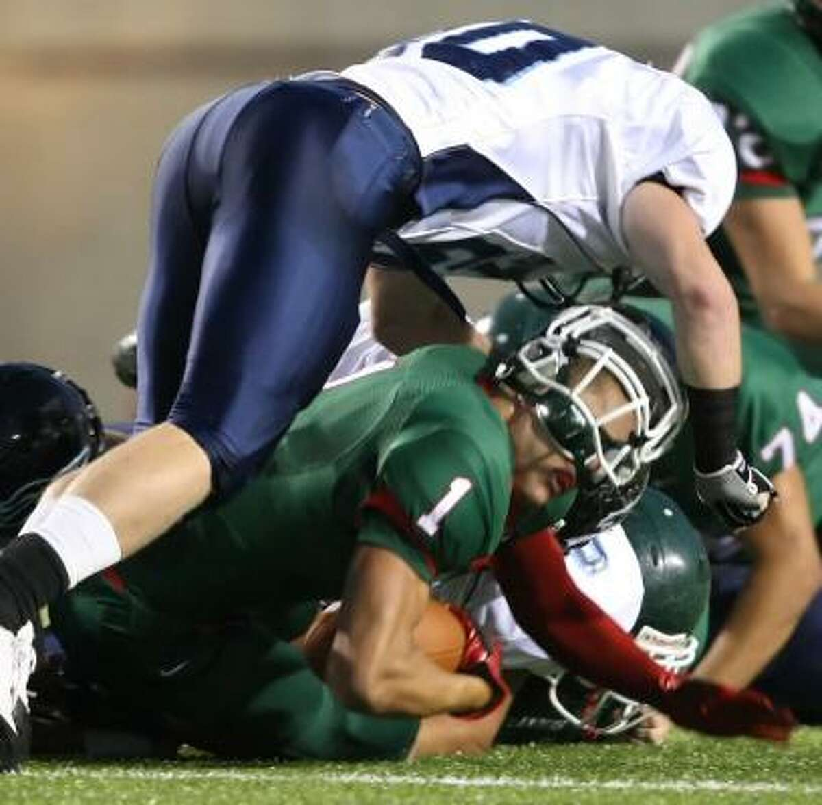 The Woodlands' Daniel Lasco is popped by Kingwood's Tony Winslow during the first quarter.