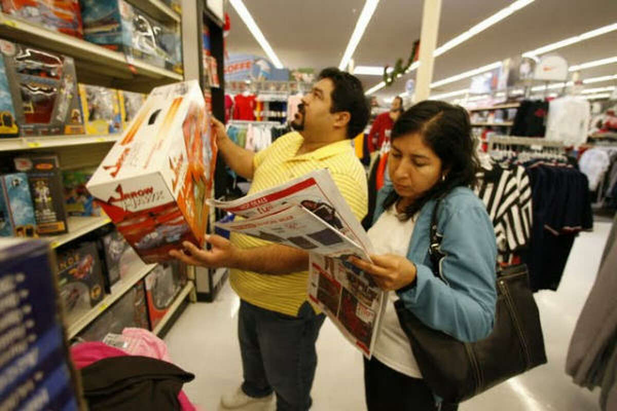 Rick Resendez and his wife Blanca scan the shelves for advertised bargains at the Academy store off Southwest Freeway and Kirby.