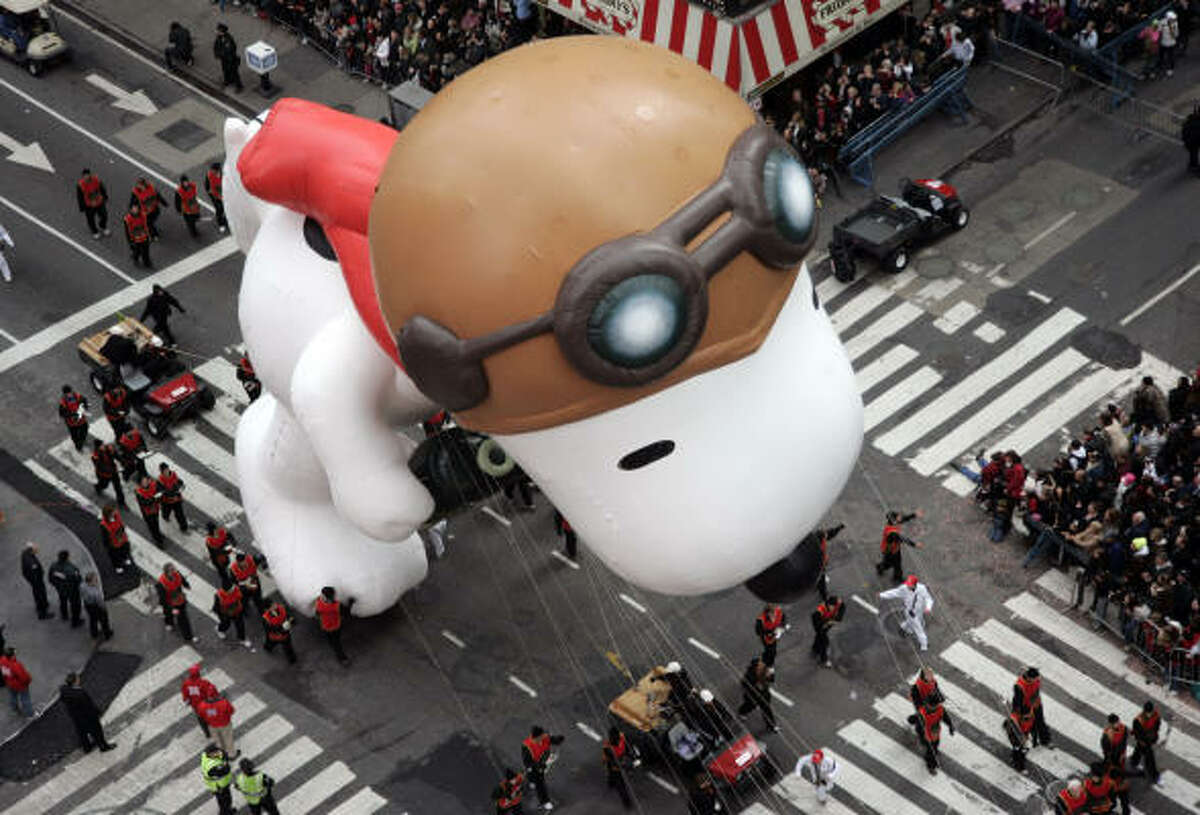 The Snoopy balloon floats through Times Square today during Macy's Thanksgiving Day parade in New York.