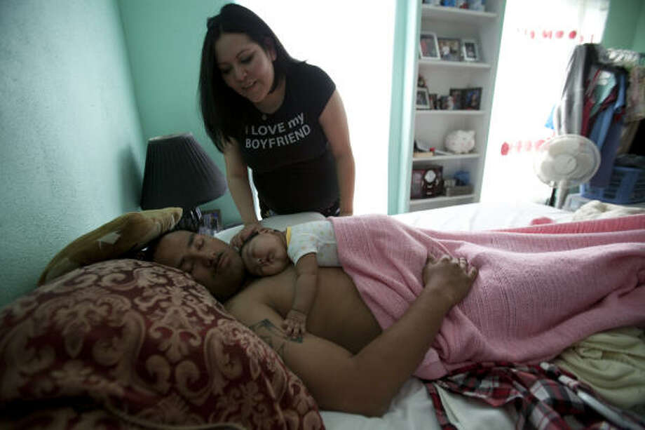 Laura Patricia Gonzalez tries to wake up her future husband Spc. Antonio Hernandez, who is sleeping with their three-month-old daughter, Karen Alicia Hernandez, on their wedding day.  Spc. Hernandez will be deploying with Texas National Guard's 72nd Infantry Brigade Combat Team. They are preparing for a year-long deployment, including nine months in Iraq. Photo: Mayra Beltran, Chronicle