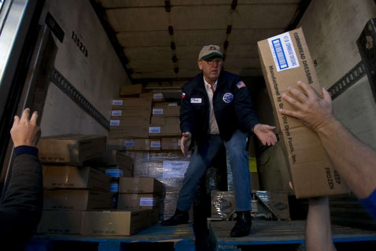 Gary Smith, with Wal-Mart, collects boxes of cornbread dressing that will be used for tomorrow's Superfeast. The annual event held outside of Houston City Hall will serve 9,000 pounds of turkey, 4,000 pounds of dressing, 400 gallons of gravy, 4,000 pounds of whole cranberries, 4,000 pounds of green beans, 4,000 pounds of corn and more than 21,000 servings of cakes and pies.