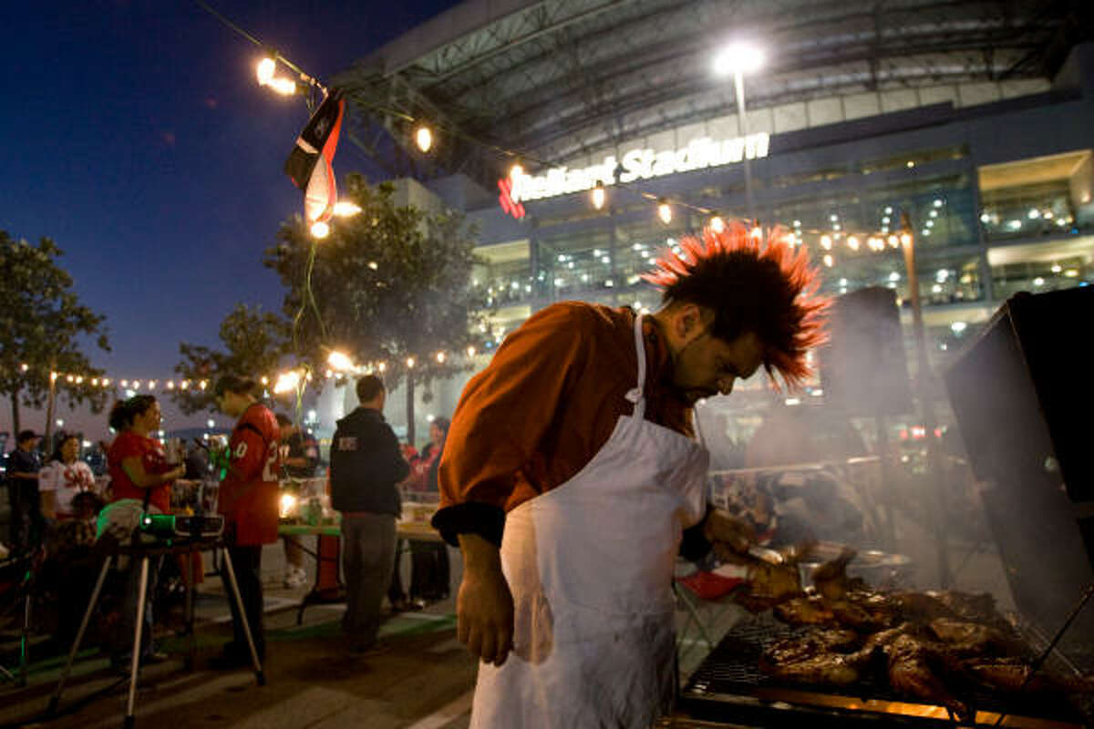 A tailgater cooks in the parking lot before the game.