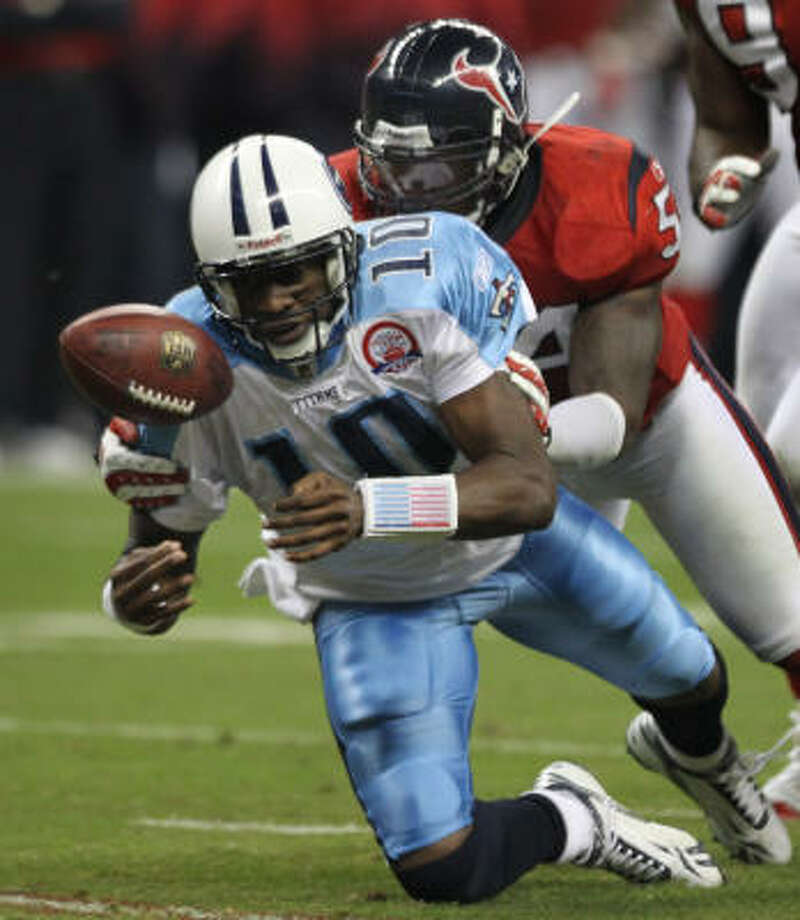 Titans quarterback Vince Young fumbles as he is hit by Texans linebacker Zac Diles during the third quarter. Photo: Brett Coomer, Chronicle