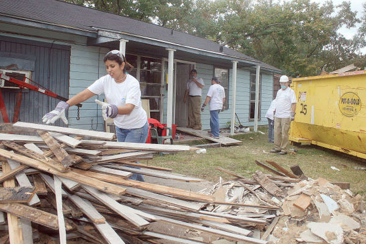 ARAMARK VOLUNTEERING: Margarita Perez clears away pieces of rotting wood taken out of the house. ARAMARK employees volunteered to will help remodel and repair several homes in the Sunnyside/South Park neighborhoods, including the home of Lorene Bell.