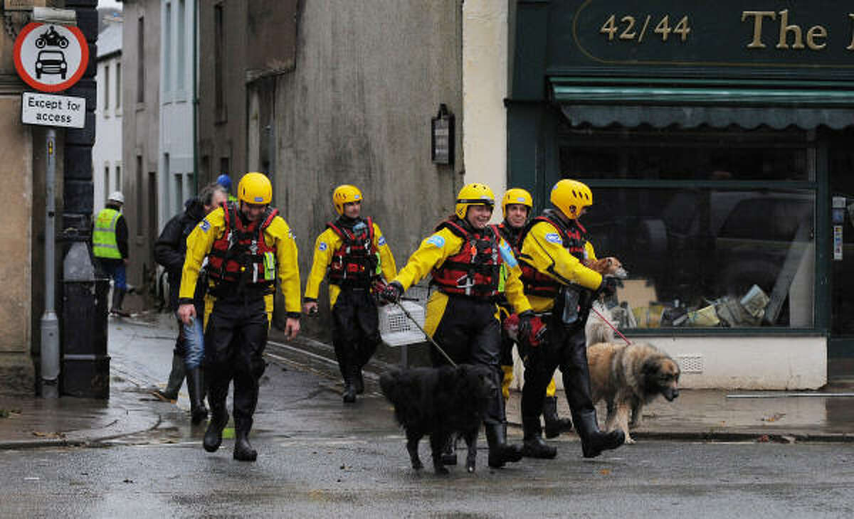 Royal Society for the Prevention of Cruelty to Animals Inspectors return dogs to their owners in Cockermouth, northwest England, Nov. 21, that were rescued after flooding.