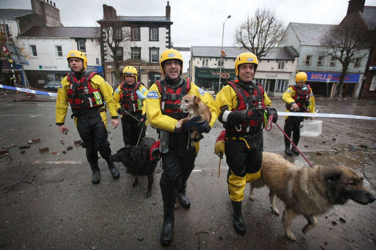The dogs Smudge, Kerry and Molly were stranded in their flooded homes after about 12 inches of rain fell in 24 hours during the week, causing floods that swept a policeman to his death and destroyed bridges.