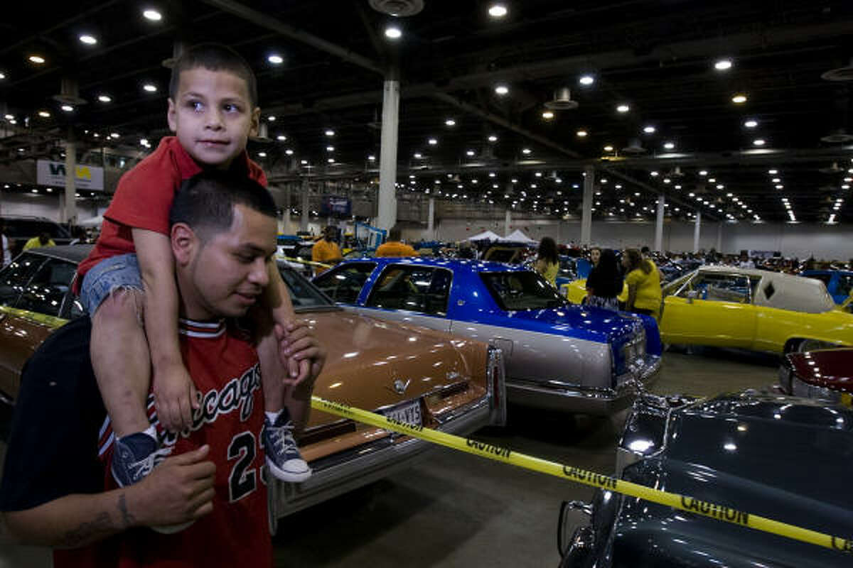 Samuel De Leon, 22, and his son, Jayden, 4, admire lowriding vehicles.