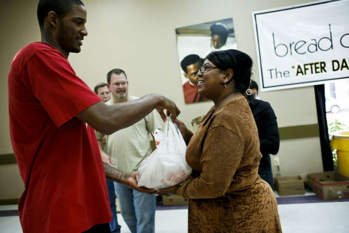 Rockets forward Trevor Ariza greets Sheila Hill as he helps give away 100 Thanksgiving dinners, including turkeys, at the Bread of Life Family Community Health Center on Sunday. Ariza wanted to help out families in need during the holiday season. Members of Crosspoint Church also volunteered by helping to fill grocery sacks and carry the items out for those in need.