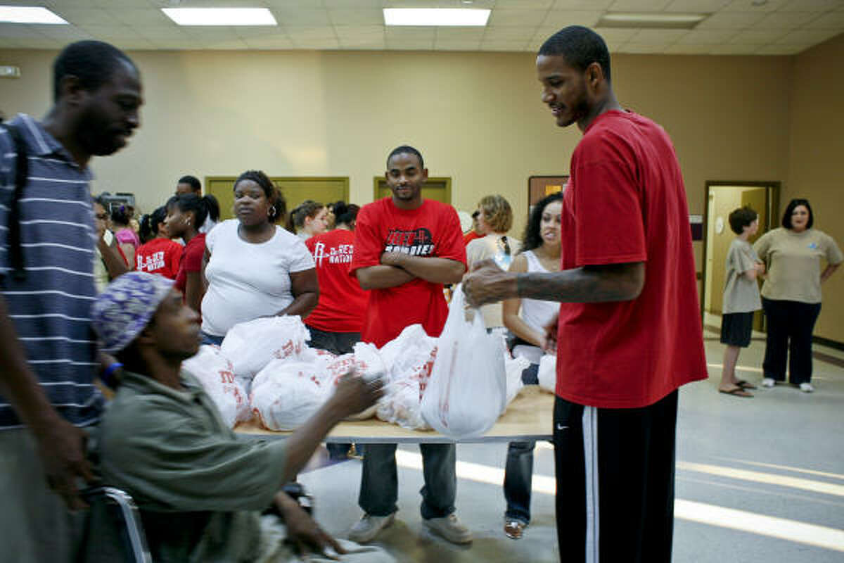Rockets forward Trevor Ariza, right, hands a turkey to Larry Simpson, left, as he's helped by volunteer Keith Fills.