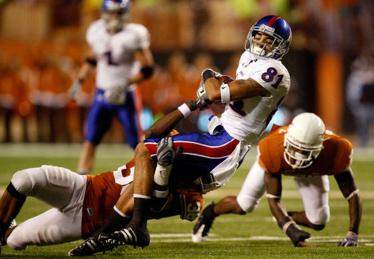 Kansas receiver Johnathan Wilson (81) is upended by Texas' Roddrick Muckelroy.