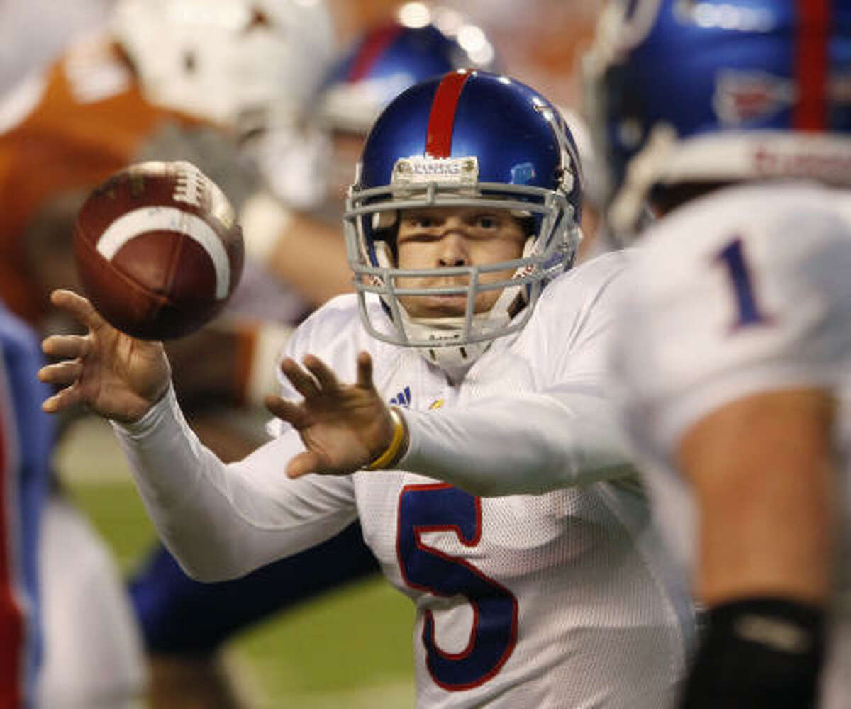 Kansas quarterback Todd Reesing, left, hands the ball off to teammate Jake Sharp during the first half.