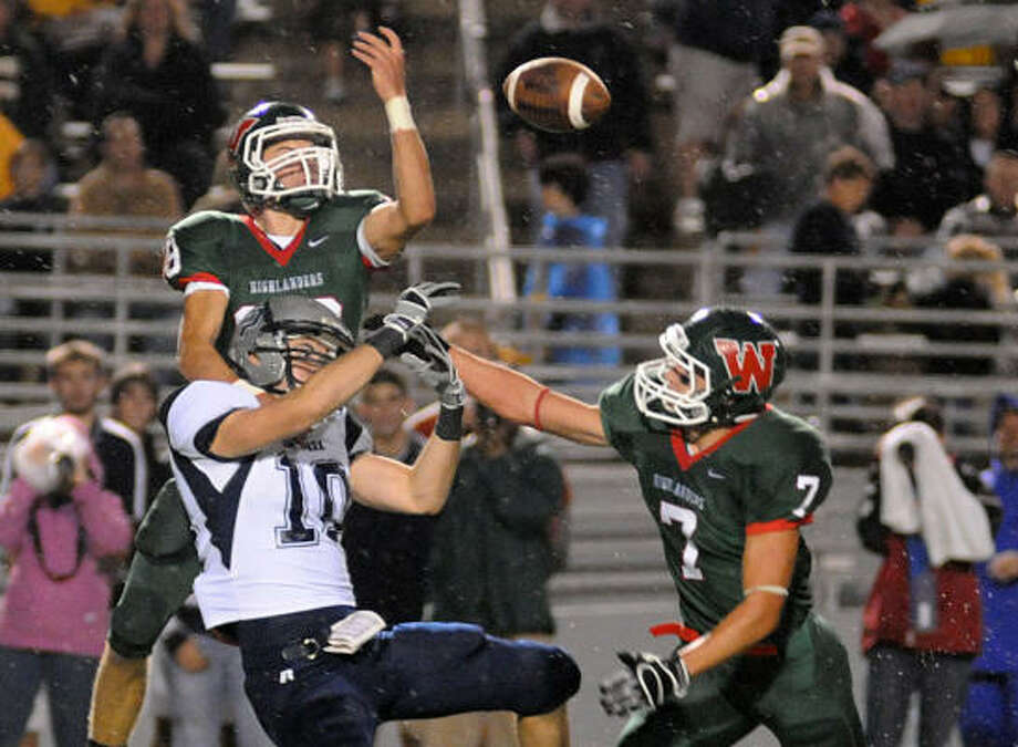 The Woodlands' Ryan Clapsaddle, with help from Ryan Kretchmar, breaks up a pass to College Park's Bret Mooney. Photo: David Hopper, For The Chronicle