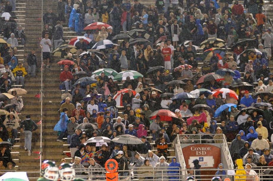 The College Park crowd tries to keep dry during the College Park at The Woodlands football game. Photo: David Hopper, For The Chronicle