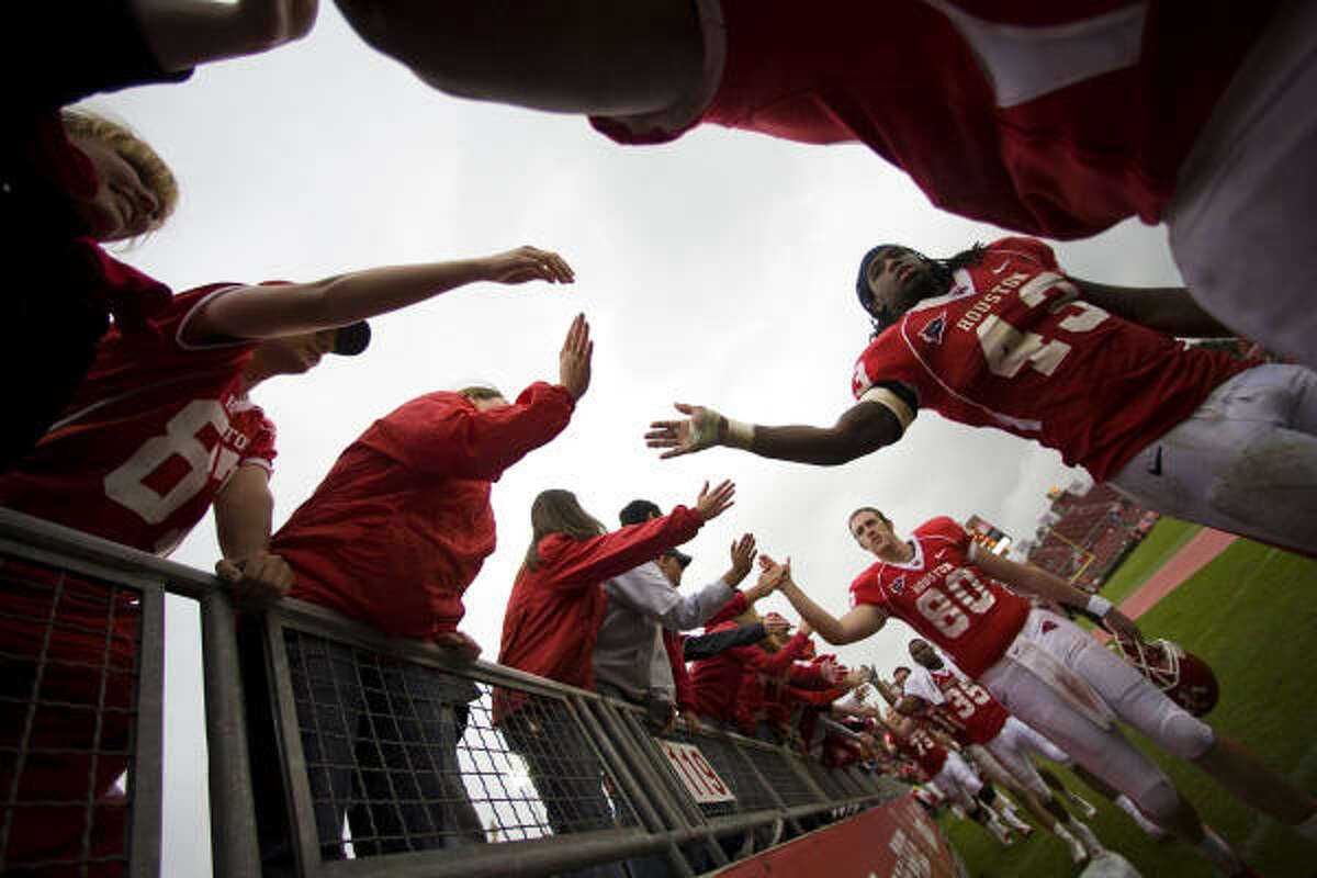 Houston defensive end Tyrell Graham (43) and the rest of the Cougars high-five fans after the victory.