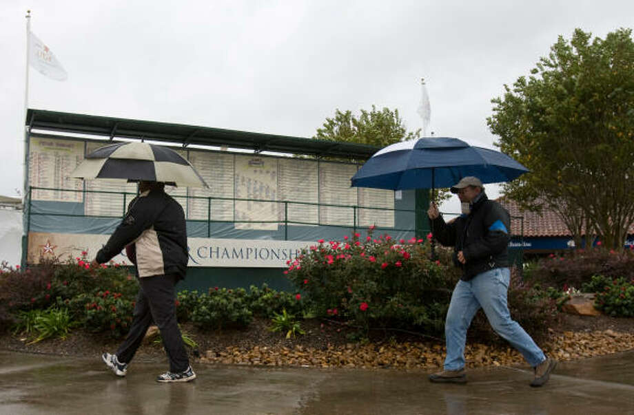 People pass by a plastic-covered leader board during the rain delay Saturday at the LPGA Tour Championship at The Houstonian Golf & Country in Richmond. Photo: Melissa Phillip, Chronicle