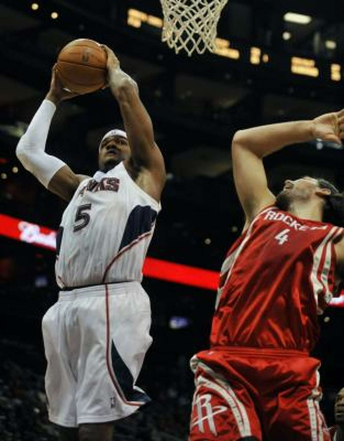 Hawks forward Josh Smith (5) takes a shot against Rockets center Luis Scola during the first quarter.