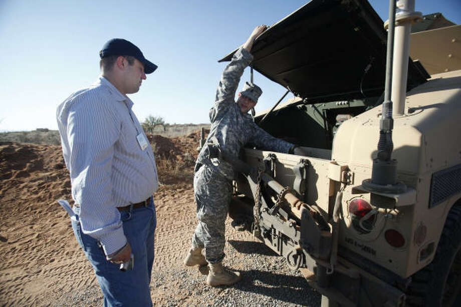 Dustin Dickschat, of Irving, listens to employee and soldier 1Lt. Kaleb Oldham as he explains mechanics of the humvee used in an IED iteration at Camp McGregor. Photo: Mayra Beltran, Chronicle